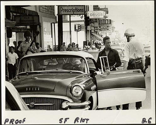 Police officer talking to a man during the 1966 Bayview-Hunters Point riots on Third Street at Palou Avenue AAK-1658.jpg
