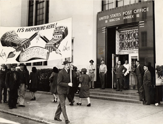 Artist Anton Refregier and C.I.O. longshoremen union members carrying a banner in protest for the covering up of a section of a mural at the Rincon Annex Post Office May 14 1948 AAK-0709.jpg