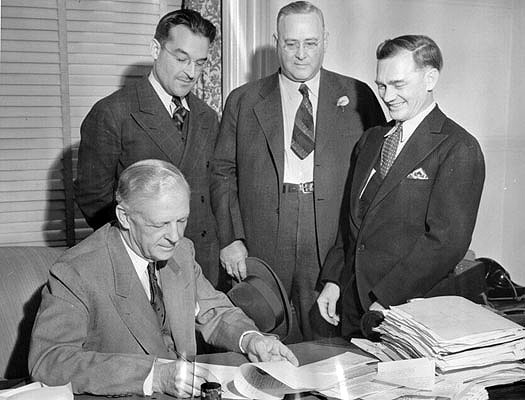 Governor-Culbert-Olson-signing-papers-which-opened-the-prison-gates-for-Warren-K-Billings-Oct-1939-AAA-5491.jpg