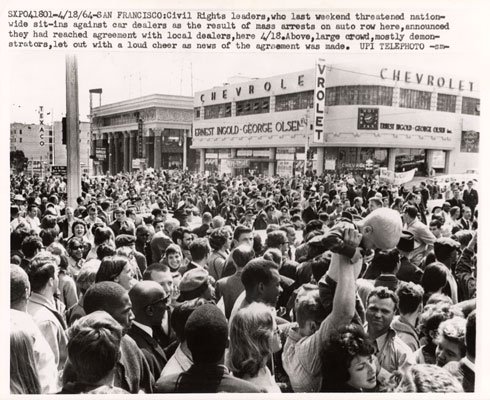 Crowd cheering settlement with auto dealers 1964 AAK-0884.jpg