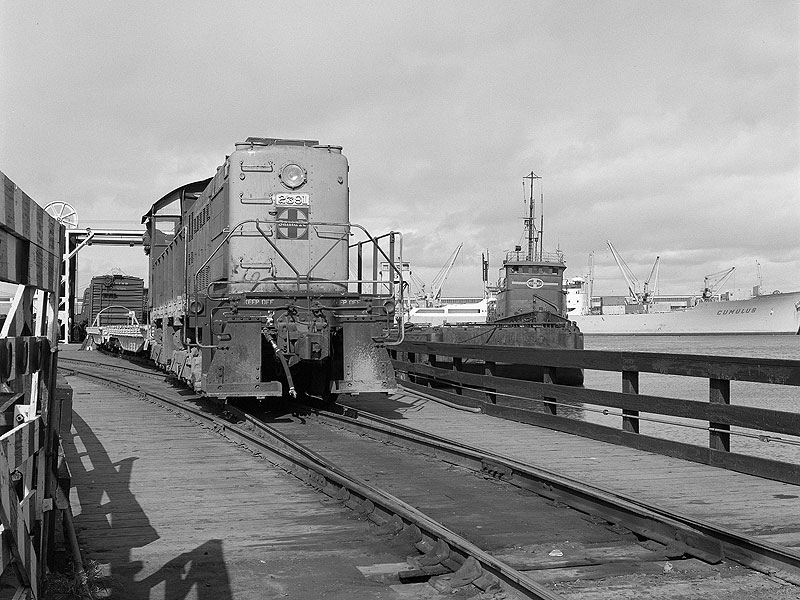 The-photographer-repositions-closer-to-the-car-float-apron-while-2381-passes-by-the-tug-Paul-P.-Hastings-as-she-pushes-freight-onto-barge-8.-Western-Railway-Museum-Archives.-Jeff-Moreau-collection.-Circa-March-1971 88515atsf-1.jpg