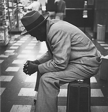Black-man-on-suitcase-left-profile.jpg