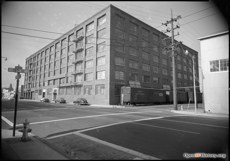 File:C 1955 View toward Northeast Corner of 15th and Folsom. Woolworth Company warehouse with railroad boxcars on 15th, presently occupied by the University of California San Francisco Mission Center. wnp100.00107.jpg
