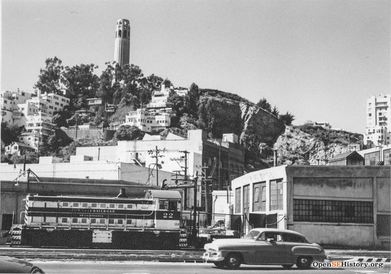 C1957 View west from The Embarcadero near Lombard toward Telegraph Hill. Belt Line locomotive 22 and Belt Line Railroad roundhouse at right, Julius Castle and Coit Tower in the background wnp27.3268.jpg