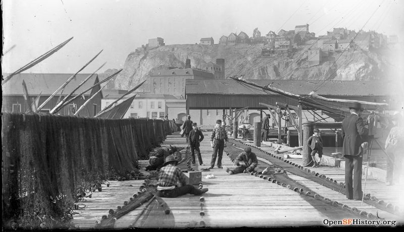 1910 View West from Union Street Wharf (then Fisherman's Wharf) toward Telegraph Hill in background. Men mending fishing nets, boys posing wnp15.1663.jpg