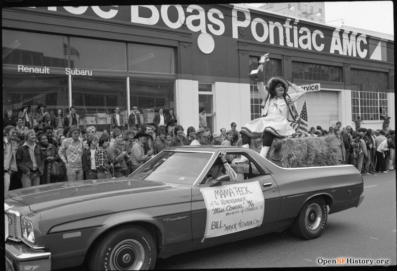 Gay Freedom Day Trophy-bearing individual on hay bale in automobile during Gay Freedom Day parade. Sign reads- Mama Peck of the Roadrunner- Miss Cowgirl 74-75, Duchess of OFarrell St. Bill, Mayor of Central City wnp72.103.jpg